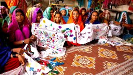 Young women seated on the floor of a room in colorful clothing and headscarves hold up a quilt they made.