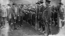 Men in uniforms surround a line of young Boy Scouts.