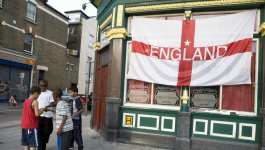 A group of four boys of diverse ethnicities gather on a sidewalk in front of a pub window that is displaying the Cross of St. George.