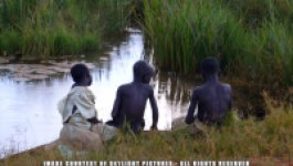 Three Ugandan children, two of them shirtless, sit by a stream during a rainstorm.