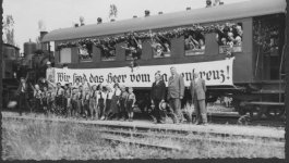 Several children salute from the windows of a train car, with some children and supervisors posing in front of the train.