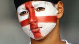 In India, a cricket fan paints his face with white and red paint to show his allegiance to England.