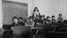 A nun stands in the back of a classroom, and children are posed sitting at desks with their hands folded.