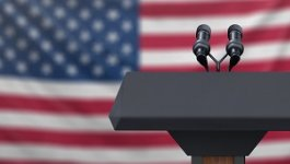 A lectern with microphones and an American flag in the background.