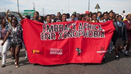 """Group of black South African protestors carrying a red banner that says """"EMBRACE AFRICA. END XENOPHOBIA"""""""