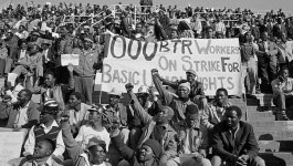 "Group of black South African miners in bleachers protesting and holding a banner ""1000BTR Workers on Strike for Basic Union Rights"""