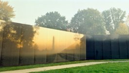 A view of the Vietnam Veterans Memorial Wall in Washington, D.C., with the Washington Monument and visitors reflected in the polished stone.