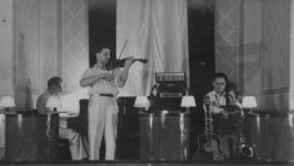 Three musicians on stage playing a piano, violin, and cello.