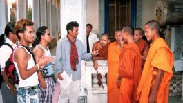 A group of Cambodian men speak with Buddhist monks at the Wat Bo Temple.