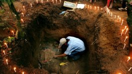 A man crouches in a grave, which is surrounded by candles, to work on exhuming a body.