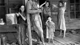 A man and four girls stand on a porch, wearing torn and dirty clothing.