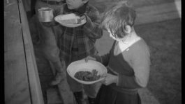 Two children hold plates with arms outstretched, seeking food.