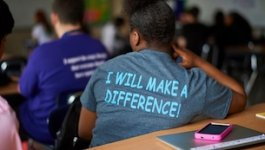 "View of a classroom from the back with a focus on a students t-shirt, which reads, ""I will make a difference."""