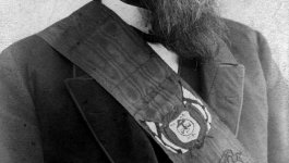 Portrait of bearded white man in a suit wearing a sash with an official crest.