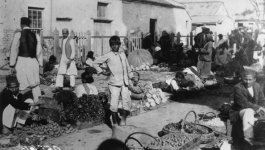 An uncovered outdoor fruit market with baskets of fruit on the ground and men, women, and children buying and selling fruit.