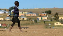 Black South African girl, wearing a school uniform and a backpack, walking on a dirt road.
