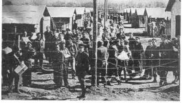 Prisoners line up between two long rows of buildings. A wire fence holds them in the foreground.
