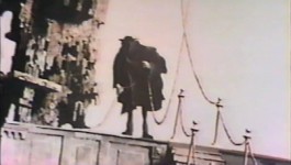 The Hangman stands next to the gallows with a rope in his hands.