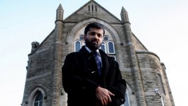 A portrait of Sheraz Arshad in front of the Mount Zion Methodist Church.