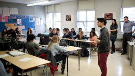 Image of student talking in front of class of peers.