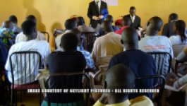 Two men in suits, one standing and speaking, and one sitting, address an audience of Ugandans in a room with bright yellow walls.
