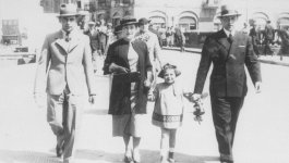 Three adults and a young girl walk on a city street.