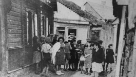 Photograph of a group of Jewish women conversing in an alley outside the only barbershop in the Kovno ghetto.