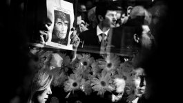 A photo of slain Turkish-Armenian journalist Hrant Dink is seen in the reflection of the hearse carrying his flower-covered coffin during a funeral procession.