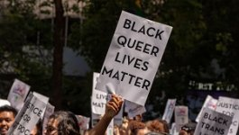 """A group of people gathered outside, one holds a sign reading """"Black Queer Lives Matter"""""""