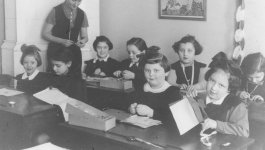 Teacher and young female students in a Jewish elementary school classroom.