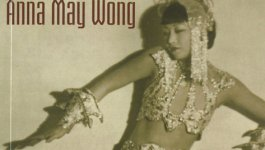 The cover of biography of Anna May Wong by Graham Russell Gao Hodges. Shows Anna May Wong posing in a  beaded gown and headpiece.