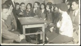 A group of approximately twenty young men and women cram together around a desk. Circa 1930s.