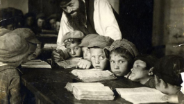 A group of elementary school students look at their notebooks as a teacher helps one of them. Circa 1920s Poland.