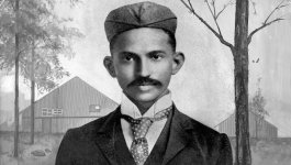 A front-facing portrait of a young Indian man wearing a suit and a cap in front of a painted landscape of trees and buildings.