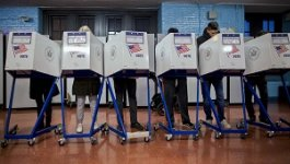 A line of U.S. voters submitting their ballots behind privacy screens.