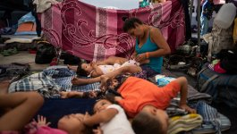 A woman changes a child in a tent, with other children lying on the floor in front of them.