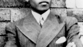 Young, black South African man with his arms crossed and a serious look on his face, wearing a pinstripe suit.