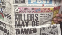 """Black South African woman reading a newspaper with the front page headlines """"KILLERS MAY BE NAMED"""""""