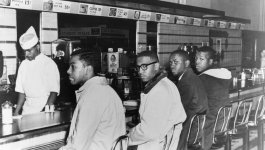 Four African American college students sit at a lunch counter during a sit-in.