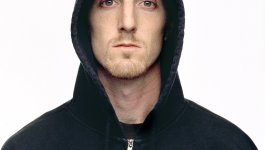 Photo of young white man with light facial hair, and dark hoodie zipped and with hood up.