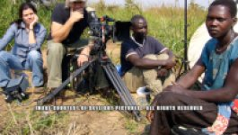 A film crew of three people film an interview. They sit on the ground in the background with equipment, and the interviewee, a black Ugandan woman, sits in the foreground.