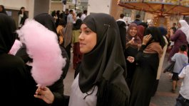 A Muslim girl wearing a hijab holds a stick of cotton candy while she stands in a crowd of people.