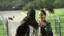 On a sunny day, two students, one wearing a veil and a backpack, clasp hands in a gesture of support.