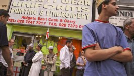 A teenage British Bengali boy stands in front of a storefront. More people gather in the background.