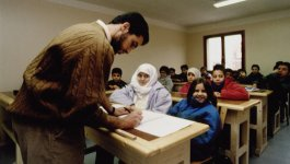 A teacher stands before his class, which is full of Muslim students, with some veiled girls.
