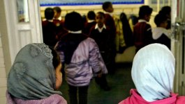 Two Muslims girls wearing headscarves walk through the door to a room crowded with a diverse group of students.
