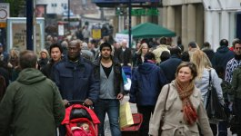 A crowd of people of many enthicities walk on a street in Britain.
