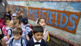 A group of diverse students gather outside next to a wall with a Millfields mural. Circa 2006.
