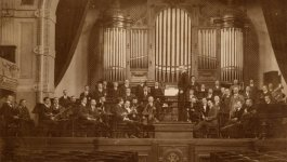 A full orchestra on stage with a pipe organ in the background, circa 1930s.
