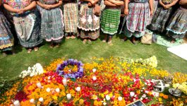A group of people in colorful clothing pray next to flowers, candles, and photographs of their deceased relatives.